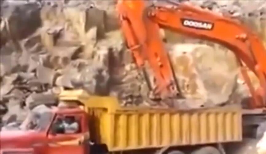挖掘机这样给卡车丢大石头装料,吓得货车司机马上跳下车!