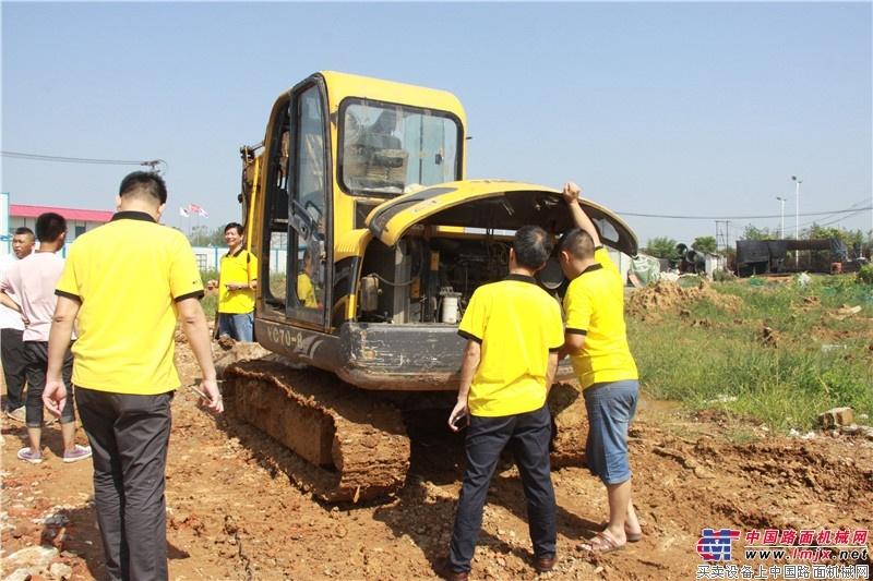 烈日下服务人员仔细检查挖机