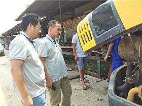 服务人员检查挖掘机使用情况