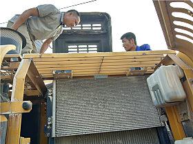 服务人员检查挖掘机的电路